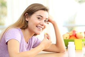 Happy teen taking omega 3 pill
