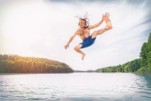 Young fit man making a jump into a lake.