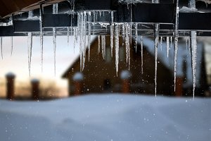 Beautiful icicles on a background of a country house and snow snowdrift. Snowing, winter