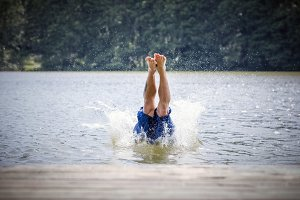 Young man diving into a lake.
