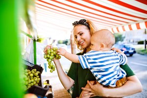 Young mother with her baby boy at outdoor market.