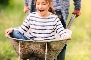 Grandfather pushing his grandaughter in a wheelbarrow.