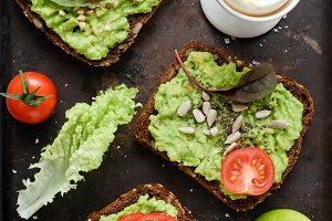 Healthy green veggie toast with avocado, tomato, sprouts and seeds and boiled egg on rusty background
