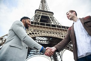 Two Men Shaking Hands By The Eiffel Tower In Paris