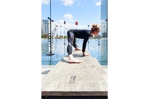 Woman Doing Yoga Near Lake In Urban Setting, Paris