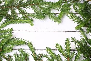 frame with spruce branches white wooden background