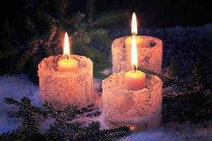 burning candles on a winter background