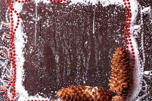 frame snow with fir cones and Christmas beads on a dark wooden background snowy winter brochure