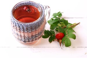 Tea with rosehip knitted in a mug on a white wooden background with space for text view from above a flat view autumnal time