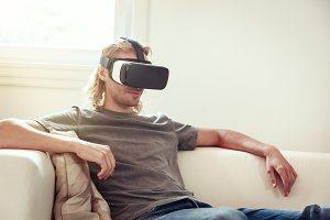 Young Man Sitting On Couch, Using Vr Glasses