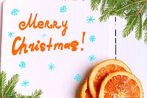 New Year background Christmas tree with cutting board with the words Merry Christmas and with dried oranges on a white wooden view from above greeting Winter brochures, postcards, magazines