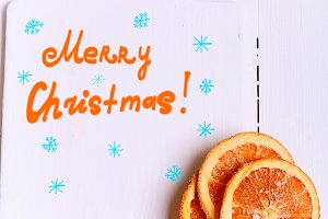 New Year background cutting board with the words Merry Christmas and with dried oranges on a white wooden view from above greeting Winter brochures, postcards, magazines