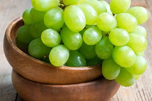 Bunch of green ripe grapes in wooden bowl, square