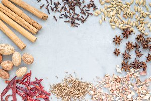Different kinds of aromatic winter spices on a gray concrete background, top view, copy space, horizontal
