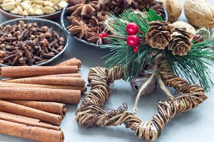 Different kinds of aromatic winter spices and christmas decoration on gray concrete background, horizontal