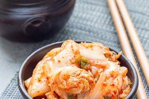 Kimchi cabbage. Korean appetizer in ceramic bowl, vertical