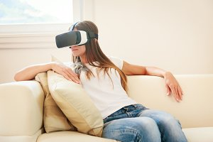 Young Woman Sitting On Couch, Using Vr Glasses