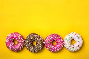 Four donuts in line on yellow background