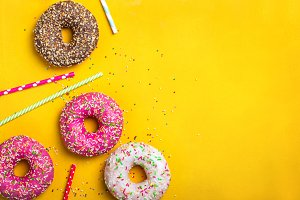 Yellow dessert background with various donuts