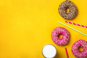 Yellow dessert background with various donuts and milk