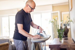 Adult Man Ironing His Shirt