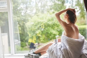 a woman sits on a windowsill with a cup of coffee