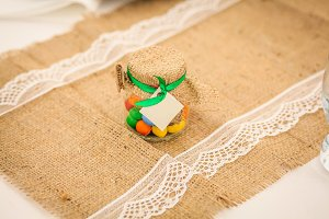 Colorful candy jar decorated with a bow against rustic burlap background. Birthday concept