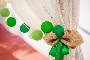 Cotton balls garland hangs on a white curtain. Bright colored decoration. Wedding