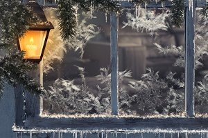 Beautiful winter window. Snow, icicles. Yellow lantern