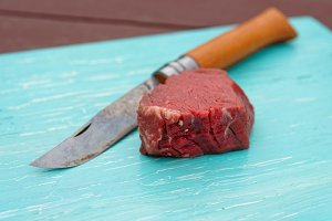 Raw tenderloin steak and knife
