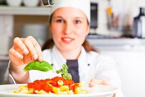 Female Chef Finishing A Pasta Dish