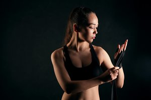 Athletic girl in sport top on black studio background. Attractive woman is wrapping up bandages for boxing.
