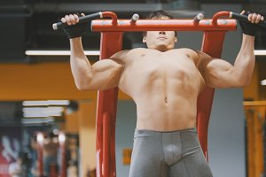 Muscular young man pulling up in a gym, close up