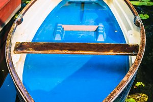 Blue colored wooden rowboat at the pier of a lake for rent surrounded by nenuphar. Municipal city park. Hamburg