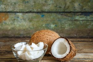 Fresh whole and half coconuts with coconut shreds