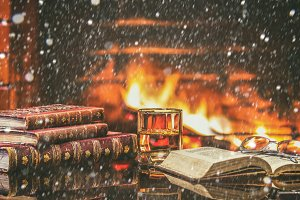 Glass alcoholic drink wine antique books in front warm fireplace