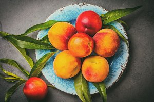 Fresh peaches on blue plate, gray slate background. top view