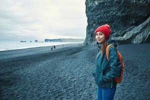 woman walking on Kirkjufjara black sand beach, southern Iceland.