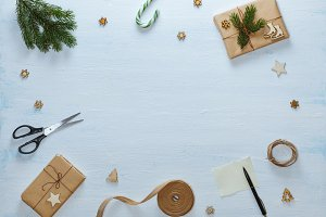 Christmas gift packaging composition. Christmas gifts, candy, fir branches, scissors, ribbon, pen with blank sheet on blue wooden background. Flat lay, top view