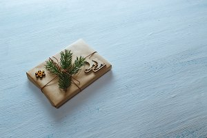 Christmas gift tied with rope, fir branches, and wooden skates on blue wooden background. Flat lay, top view, copy space
