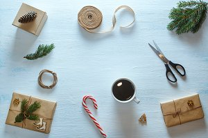 Christmas gift packaging composition. Christmas gifts, cup of tea, candy, fir branches, scissors, ribbon. Flat lay, top view