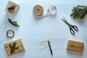 Christmas gift packaging composition. Christmas gifts, fir branches, scissors, ribbon, pen with blank sheet on blue desk. Flat lay, top view