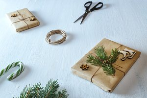 Christmas gifts, fir branches, scissors, ribbon, candy on blue desk. Flat lay, top view