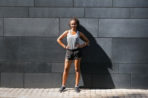 Fitness woman standing at wall