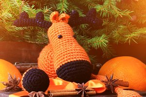 Christmas composition deer gift under the tree by hand knitted toy cinnamon, anise tangerine spruce vintage style on old wooden background