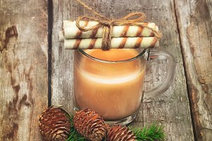 Christmas coffee with milk branch of fir with cones old retro vintage wood background