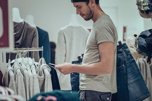 Young man choosing clothes in shopping mall