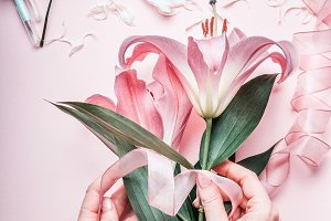 Hands making pink flowers bouquet