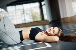 Portrait of beautiful adult woman exercising in gym looking at camera smiling laughing happy about her perfect body.