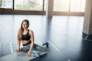 Portrait of beautiful adult woman training in an empty gym keeping her perfect body and long hair intact.